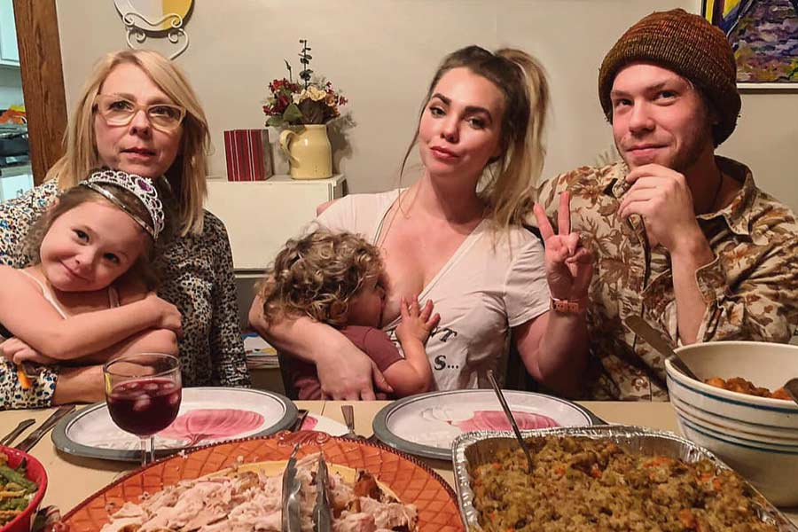 Mom Breastfeeds Her Baby Amidst A Family Holiday Dinner